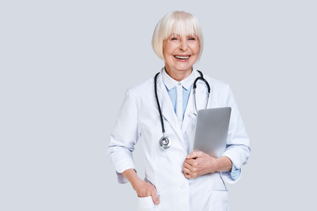Reliable cardiologist. Beautiful senior woman in lab coat looking at camera and smiling while standing against grey background Stock Photo