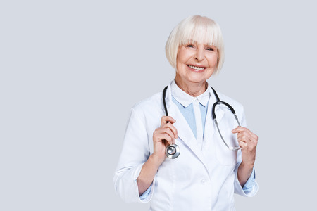 Female doctor. Beautiful senior woman in lab coat looking at camera and smiling while standing against grey background Stock Photo