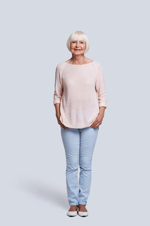 Always young at heart. Full length of beautiful senior woman looking at camera and smiling while standing against grey background