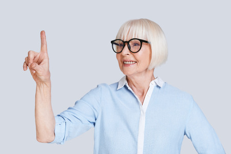 Look! Beautiful senior woman pointing copy space and smiling while standing against grey background