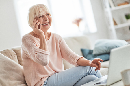 Happy to hear you! Beautiful senior woman talking on her smart phone and smiling while relaxing on the couch at home