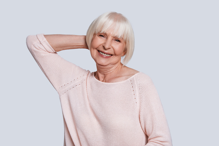 Simply happy. Beautiful senior woman looking at camera and smiling while standing against grey background