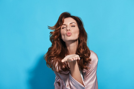 Catch! Attractive young woman blowing a kiss and keeping eyes closed while standing against blue background