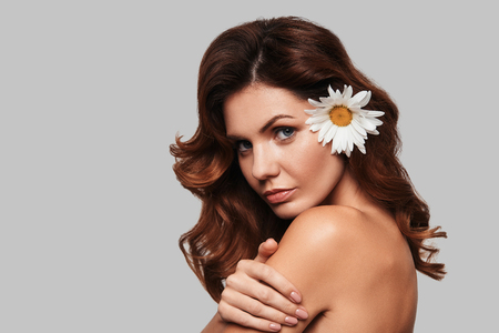 Pure beauty. Attractive young woman looking at camera and keeping chamomile in hair while standing against grey background