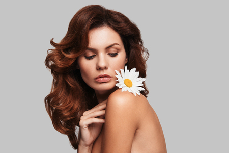 Dangerously beautiful. Attractive young woman keeping chamomile on shoulder while standing against grey background
