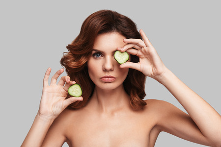 Sensitive care for a luminous skin. Attractive young woman looking at camera and covering eye with a slice of cucumber while standing against grey background