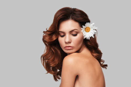 Pure beauty. Attractive young woman keeping chamomile in hair while standing against grey background Stock Photo