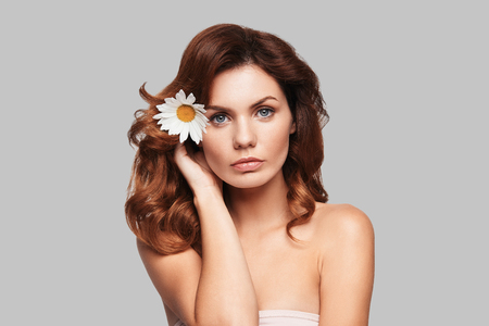 Beautiful as flower. Attractive young woman looking at camera and keeping chamomile in hair while standing against grey background Stock Photo