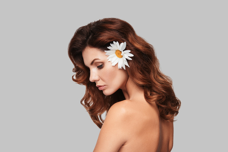 Perfect in every way. Attractive young woman keeping chamomile in hair while standing against grey background