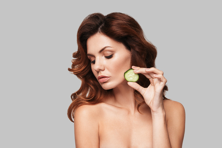 Perfect skin. Attractive young woman applying a slice of cucumber while standing against grey background Stock Photo