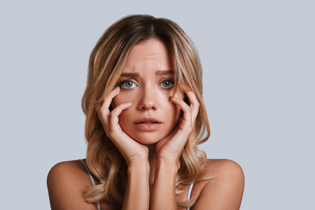 Ce qu'il faut faire? Jeune femme frustrée regardant la caméra en se tenant debout sur fond gris