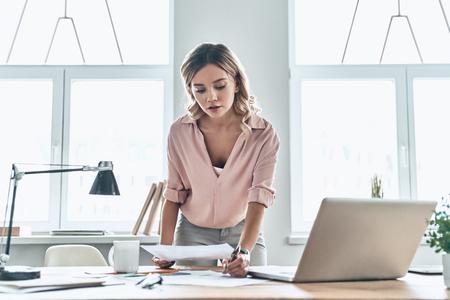 Travailler dur. Jeune femme réfléchie dans des vêtements décontractés intelligents regardant un document tout en se tenant dans un bureau moderne