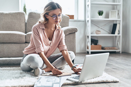 Enjoying her creative job. Thoughtful young woman in eyewear working using computer while flooring at home Stock Photo