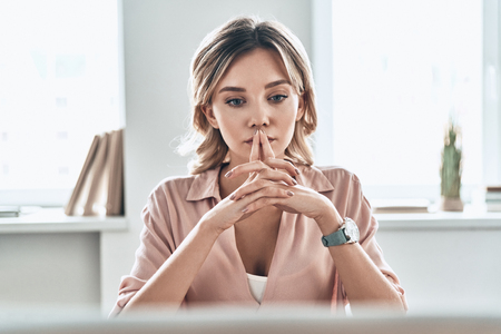 Lost in thoughts. Thoughtful young woman in smart casual keeping hands clasped while sitting in modern office