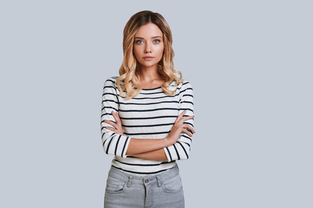 Perfect in every way. Attractive young woman looking at camera and keeping arms crossed while standing against grey background