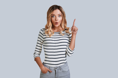Idea! Attractive young woman looking at camera and pointing copy space while standing against grey background
