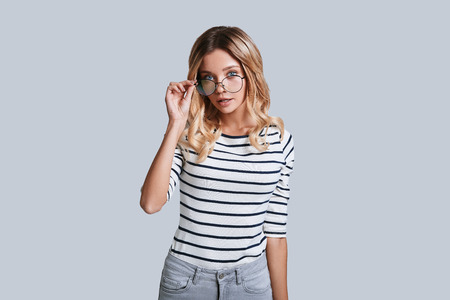 Feeling curious. Attractive young woman adjusting her eyewear and looking at camera while standing against grey background 写真素材