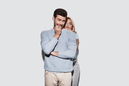 Worried about something. Terrified young couple making a face while standing against grey background