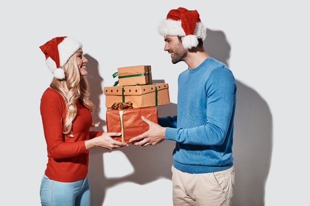 Gift to beloved. Beautiful young couple in Christmas hats holding gift boxes and smiling while standing against grey background