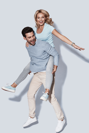 Feeling playful. Full length of handsome young man giving his girlfriend a piggyback ride while standing against grey background