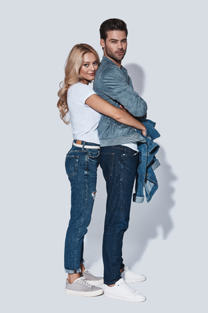 Happy moments together. Full length of beautiful young couple embracing and smiling while standing against grey background Stock Photo