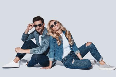 Sentimientos puros. Hermosa joven pareja en mezclilla usa pegado y sonriendo mientras está sentado contra el fondo gris