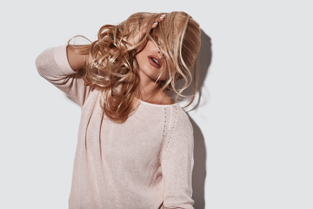 No cares. Beautiful young woman covering face with hair while standing against grey background Reklamní fotografie