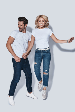 So much fun! Full length of beautiful young couple smiling while jumping against grey background Banco de Imagens