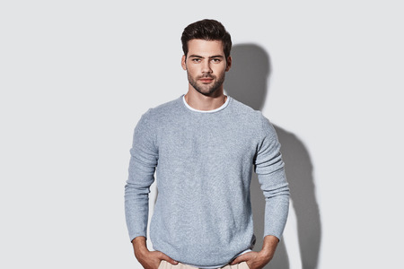 Perfect man. Handsome young man in casual wear looking at camera and smiling while standing against grey background
