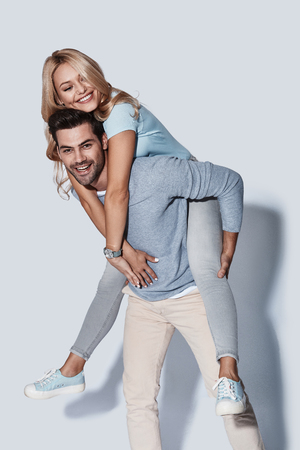 Close relationship. Handsome young man giving his girlfriend a piggyback ride while standing against grey background