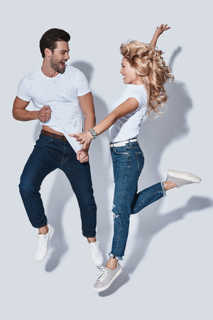 Crazy couple. Full length of beautiful young couple smiling while jumping against grey background