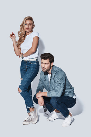 They belong together. Full length of beautiful young couple bonding while standing against grey background