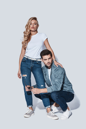 Denim style. Full length of beautiful young couple bonding while standing against grey background