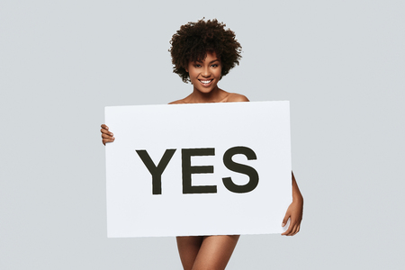 Better yes than no. Attractive young African woman holding a poster and smiling while standing against grey background