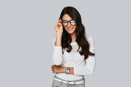 Confident and beautiful. Attractive young woman taking on her eyewear and smiling while standing against grey background Stock Photo