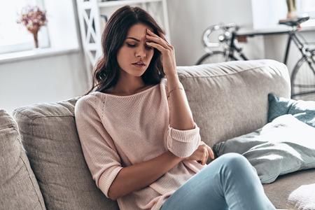 Se sentir mal. Jeune femme frustrée souffrant de maux de tête alors qu'elle était assise sur le canapé à la maison