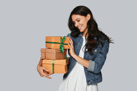 Christmas is coming... Attractive young woman smiling and carrying gift boxes while standing against grey background Stock Photo