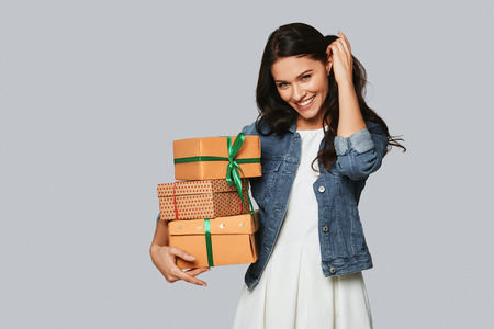 Presents for friends. Attractive young woman smiling and carrying gift boxes while standing against grey background