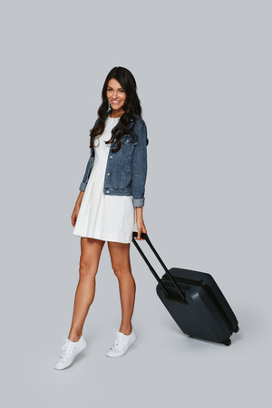Ready for trip. Full length of beautiful young woman smiling and pulling luggage while standing against grey background