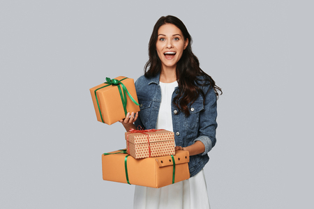 For me? Excited young woman smiling and holding gift boxes while standing against grey background Banco de Imagens