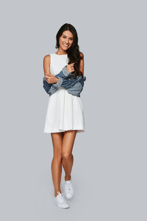 Happy smile. Full length of attractive young woman smiling and looking at camera while standing against grey background
