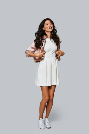 Trendy girl. Full length of beautiful young woman smiling and looking at camera while standing against grey background