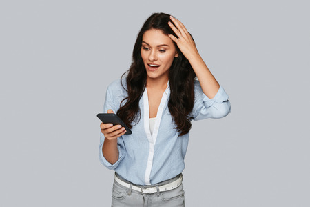Oh my God! Surprised young woman looking at smart phone while standing against grey background