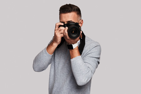Nice shot. Good looking young man photographing you while standing against grey background