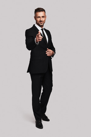 You are the one I need! Full length of handsome young man in full suit pointing you and looking at camera with smile while standing against grey background Banque d'images