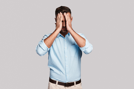 Emotional stress. Frustrated young man keeping head in hands while standing against grey background