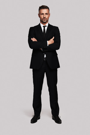 Young and successful. Full length of handsome young man in full suit keeping arms crossed and looking at camera while standing against grey background