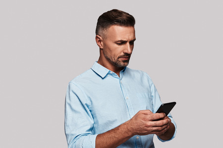 Very busy. Good looking young man in smart casual wear using his smart phone and smiling while standing against grey background