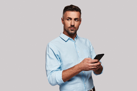 Searching for an answer. Good looking young man in smart casual wear using his smart phone and smiling while standing against grey background Banco de Imagens