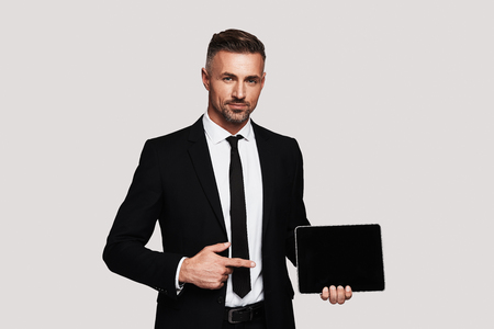 Just take a look! Handsome young man in full suit pointing copy space on digital tablet and smiling while standing against grey background